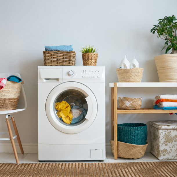 laundry machine with shelves and chair on either side